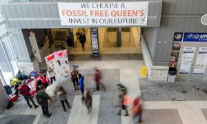 Members of QBACC hung a sign advocating a fossil fuel-free Queen's from the second floor of the ARC on Feb. 12.