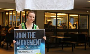 Leah Kelley holding a Blue Dot poster in the JDUC.