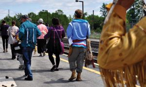 People walking down the VIA train tracks to meet the travelling artists.
