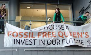 "Students holding a sign that reads ""Fossil Free Queen's"""