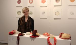 Artist Lindsey Wilson stands beside her artwork at an exhibition showcasing Queen's BFA student art.