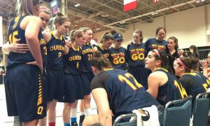 Andrea Priamo (seated, #14) speaks to her teammates during a timeout.