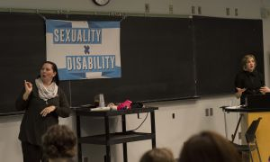 Kaleigh Trace (right) speaks to attendees of Queen's Sexuality x Disability Summit while an ASL translator signs along (left).