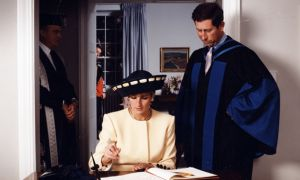 Prince Charles and Princess Diana signing the Royal guest book.