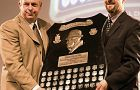 Queen's football head coach Pat Sheahan (left) accepts the Frank Tindall Trophy Friday.