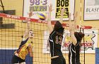 Queen's outside hitter Natalie Grey goes for a kill against Laurier's Megan Gilmore (13) and Brittany Brunt Saturday night at Bartlett Gym.