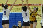 Queen's left-side hitter Louise Hamill goes for a kill against Lakehead's Karla Brayshaw (8) and Courtney Felske Sunday.