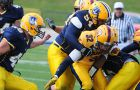 Gaels running back Ryan Granberg carries lineman Dusan Maodus on his back during Saturday's football game in Windsor. Queen's beat the Lancers 42-13.