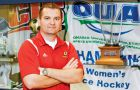 Women's hockey coach Matthew Holmberg poses with the OUA women's hockey championship trophy.