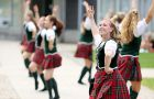 A Queen's Bands highland dancer rallies first year students in Leonard Field before the Queen's Gaels home opener.