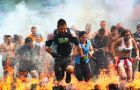 "Participants run among pits of blazing firewood for the ""Fire Walker"" obstacle during the Tough Mudder obstacle race."