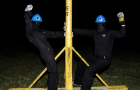 """Members of U of T's """"Brute Force Committee"""" pose with EngSoc's grease pole."""