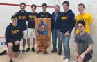 The men's squash team posing with the Jester Squash Championship banner.